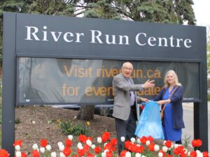 GCC President John Barnum and chorister Ardeth Jarvis standing in front of the River Run Centre sign, drawing the winning ticket from a blue bag of tickets. Red and white tulips are in the foreground.