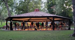 GCC members rehearse outside under a shelter at dusk